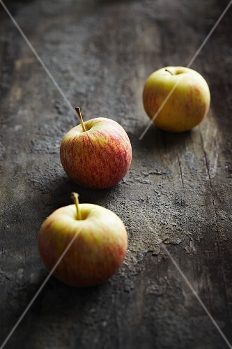 Three apples on a dark surface