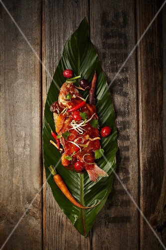 Fish with chilli and vegetables on a banana leaf (seen from above)