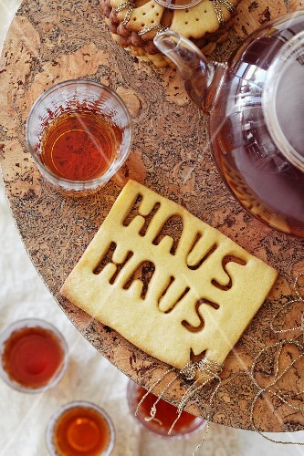 Teatime with the teapots, glasses of tea and biscuits with the word 'Haus'