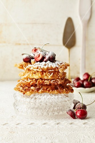 Fried pastries with icing sugar and fresh cherries