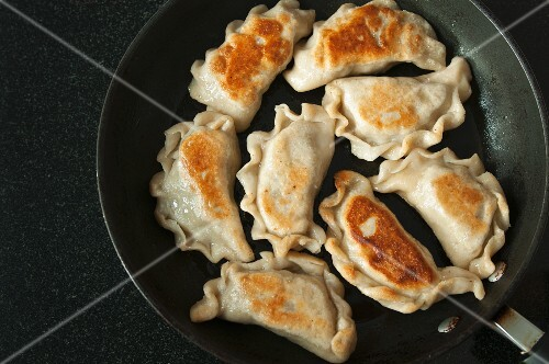 Fried pierogi (Polish meat dumplings) in a frying pan