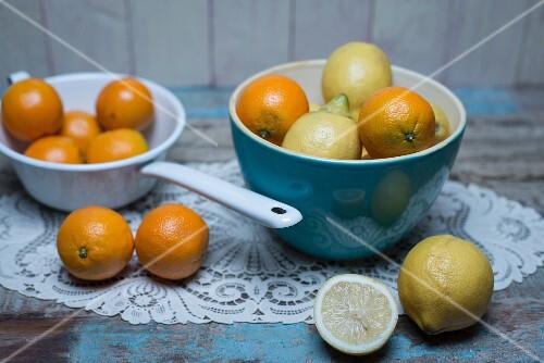 Oranges and lemons in a blue porcelain bowl and oranges in a white enamel colander