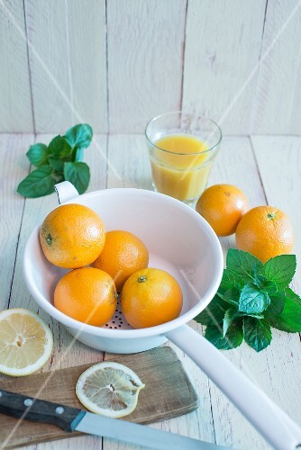 Oranges in an enamel colander, fresh mint, a glass of orange juice and sliced lemons on a board