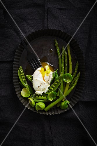 A poached egg on green vegetables (seen from above)
