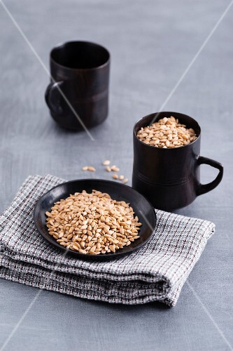 Einkorn grains in a cup and on a plate