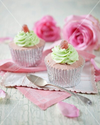 Cupcakes decorated with strawberry cream, mint frosting and jelly sweets