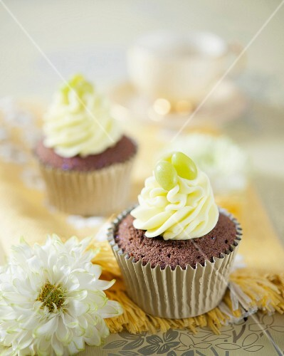 Chocolate cupcakes with vanilla frosting and green apple bonbons