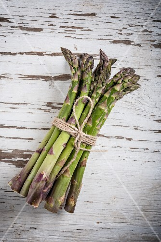 A bundle of asparagus on a white wooden surface