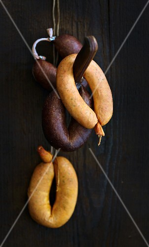 Sausages on a hook against a wooden wall