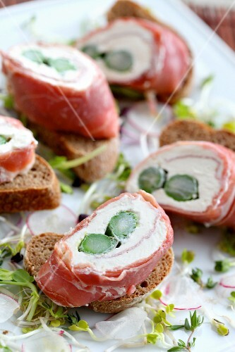 Slices of bread topped with cream cheese and ham rolls