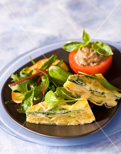 Potato omelette with a side salad and a stuffed tomato