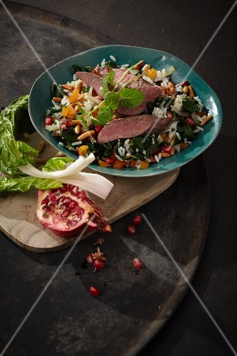 Lamb fillet with chard on a bed of rice with pomegranate seeds