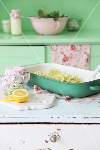 Elderflowers and lemons in green oven dish on white, vintage cabinet