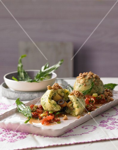 Wild herb and semolina dumplings with roasted walnut crumbs on tomato salsa and fried buckthorn
