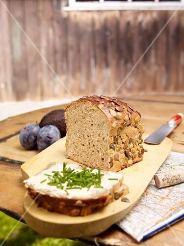 Pumpkin seed bread, sliced, on a rustic garden table