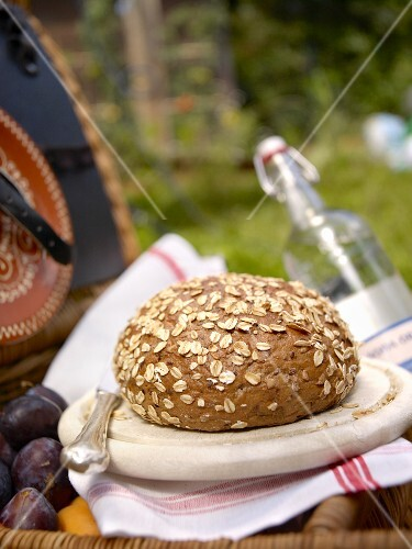 Wholemeal bread with oats on a wooden plate in a garden