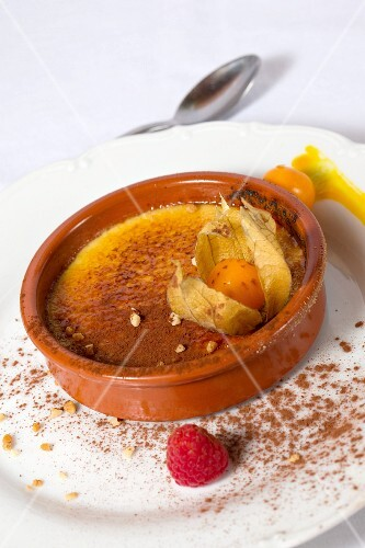 Crème brûlée with cocoa powder, physalis and raspberries