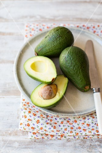 Fresh avocados, whole and halved