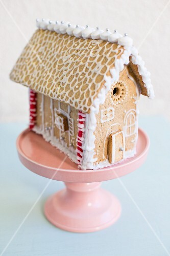 A gingerbread house on a pastel pink cake stand