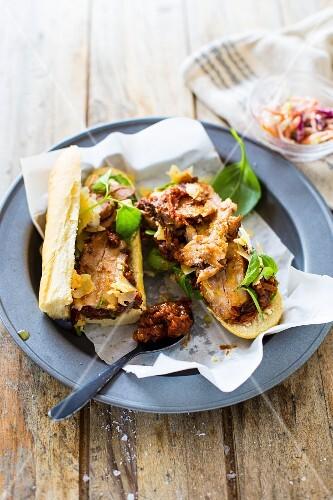 Baguette-Sandwich mit Schweinebauch, Grilltomaten-Pesto, Basilikum und Gruyere