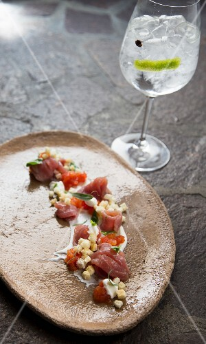 Red tuna fish with croutons served with a gin and tonic