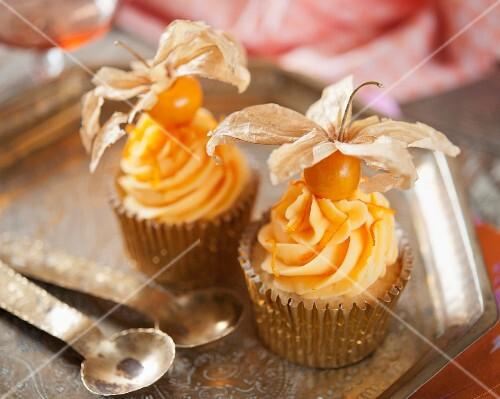 Cupcakes decorated with orange butter cream and physalis