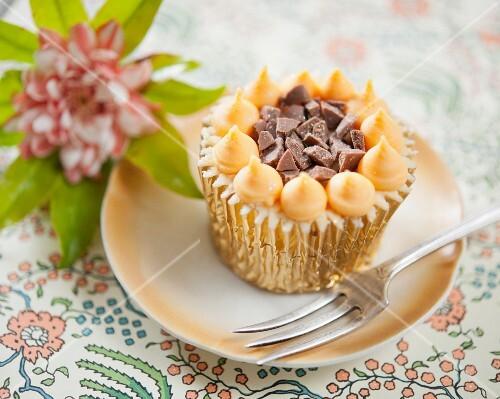 A cupcake with orange cream and chocolate chunks