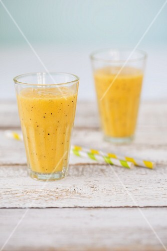 Two smoothies (mango and passion fruit, pineapple and grapefruit) in glasses