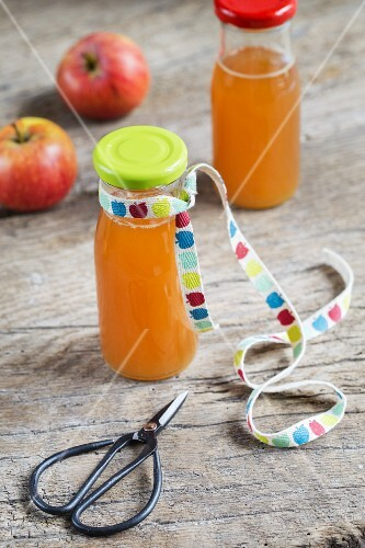 A bottle of fresh-pressed apple juice with a ribbon and a pair of scissors