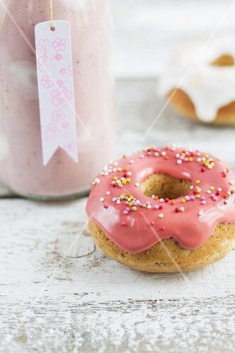A bottle of strawberry milkshake with yoghurt spots and mini iced doughnuts