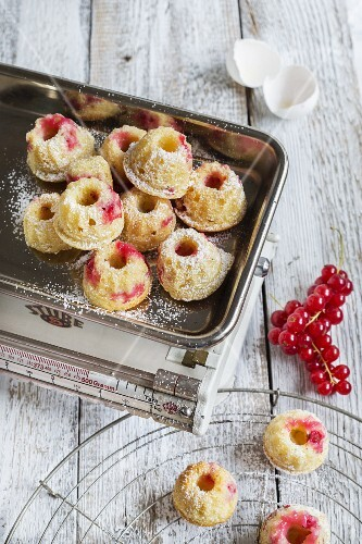 Mini Bundt cakes with redcurrants on a pair of kitchen scales with a sprig of fresh redcurrants next to it