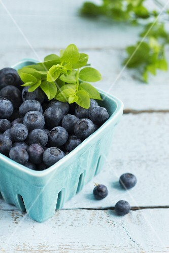 Blueberries with leaves in a turquoise punnet