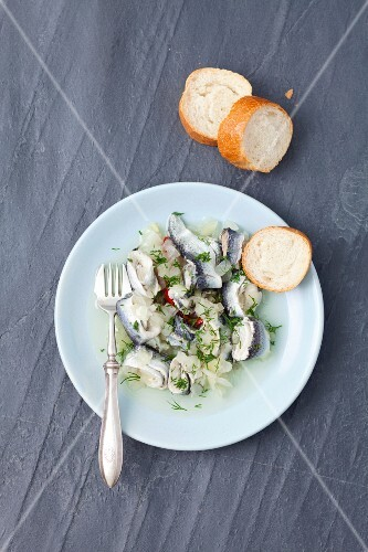 Vinegar marinated herring with onions and dill