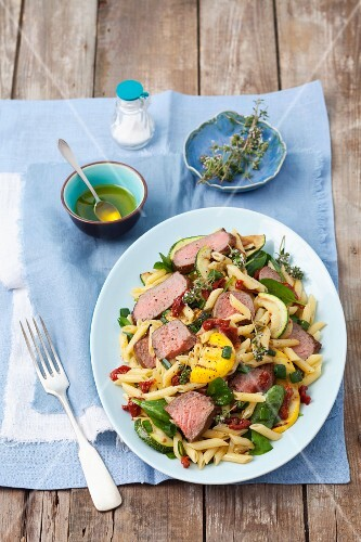 Penne pasta salad with roast beef, courgettes, dried tomatoes and spinach