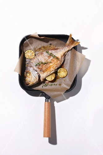 Sea bream fried in a grill pan on baking paper