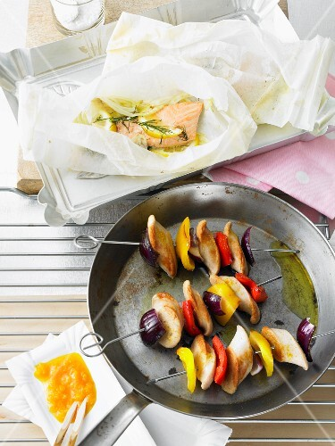 Salmon fillets in parchment paper and curried sausage skewers