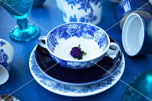 Blue plates, a soup cup, glasses and baking tins on a blue table
