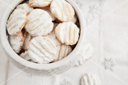 Shortbread cookies with icing sugar in a biscuit tin (Christmas)