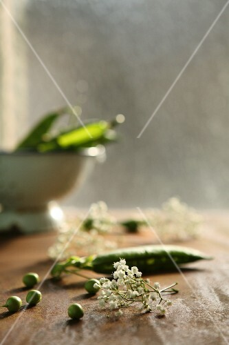 Peas and pea pods on a wooden table