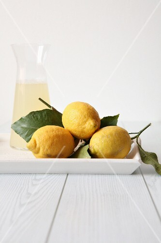 Fresh lemons, and white wine in a glass carafe