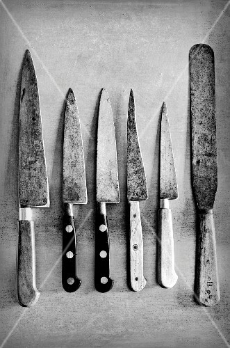 Old kitchen knives on a metal surface