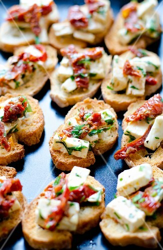 Bruschetta with feta cheese, dried tomatoes and herbs