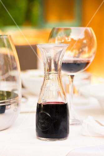 Red wine in a glass and a carafe on a laid table