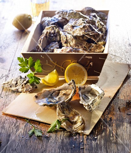 Unopened oysters in a crate and opened ones with lemon and parsley
