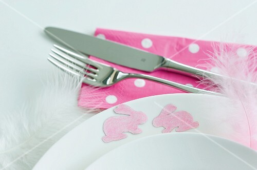 Pink bunny motifs and delicate feathers stuck to edge of plate with removable spray adhesive as Easter decorations
