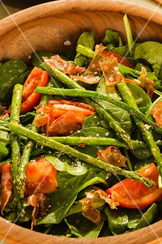 A baby spinach salad with roasted tomatoes, asparagus and ham