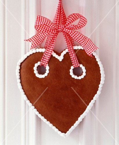Gingerbread heart with simple iced trim hung from red and white gingham ribbon