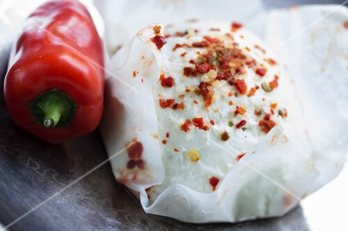Spiced goat's cheese in cheese paper and a red pepper