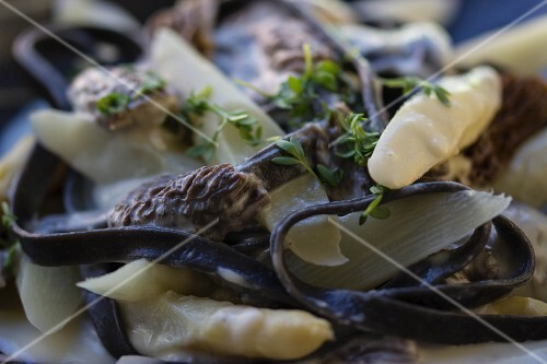 White a asparagus with black morel mushrooms, black pasta, thyme and a creamy sauce