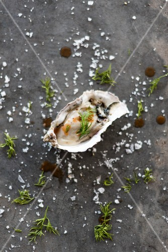 An oyster with salt and spicy sauce
